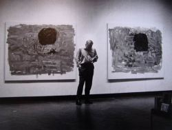 Philip Guston tweeting on his Blackberry in front of 2 of his paintings at the Saltaire open exhibition 1966